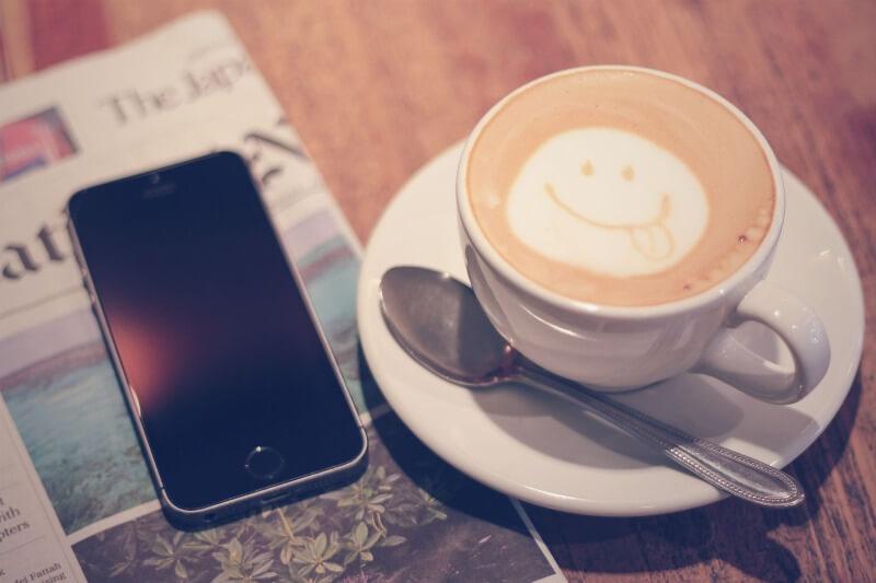 おしゃれなカフェでラテアートを飲みながらスマホを見て一息