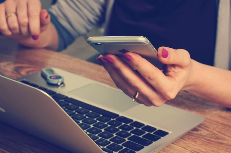 スマートフォン片手にパソコンを見る女性