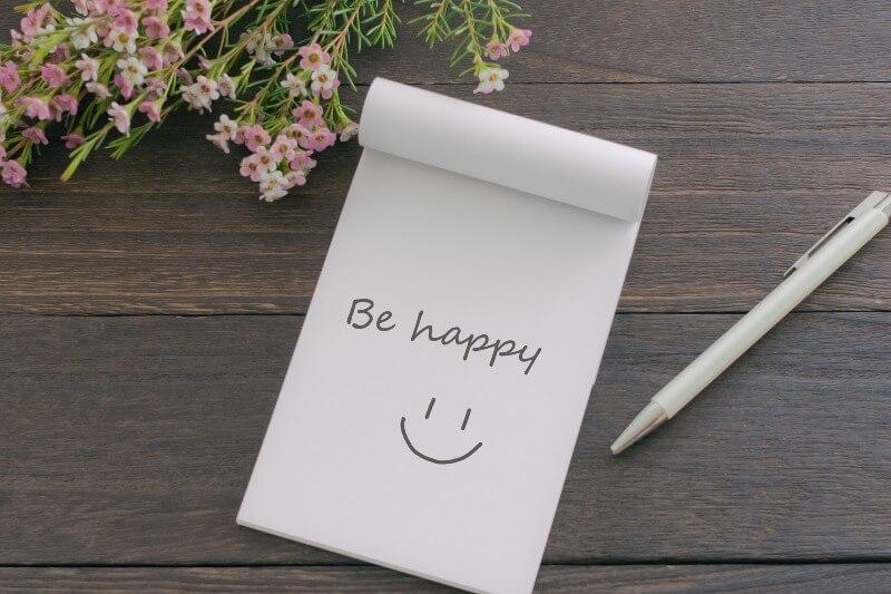 メモ帳に「Be happy」とスマイル