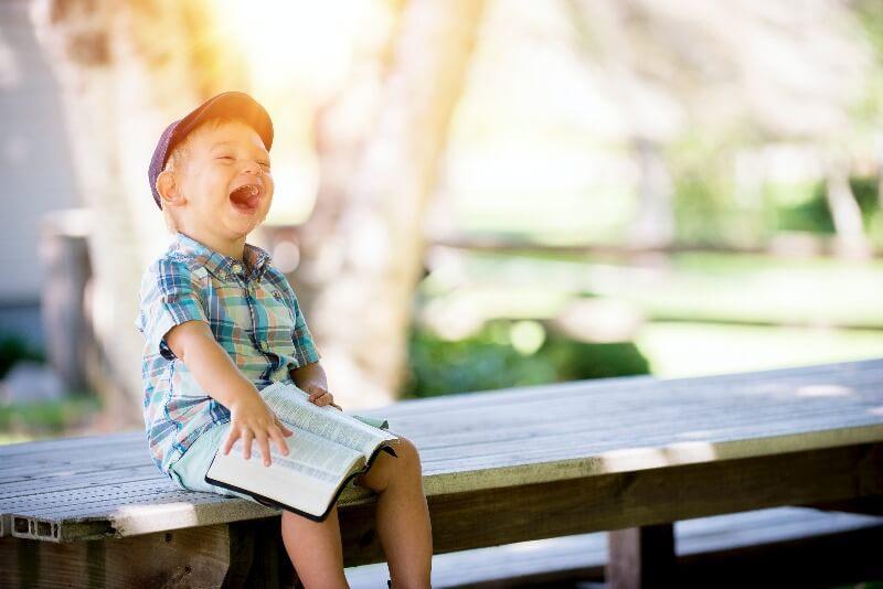 ベンチに座って本を読んでいる笑顔の少年