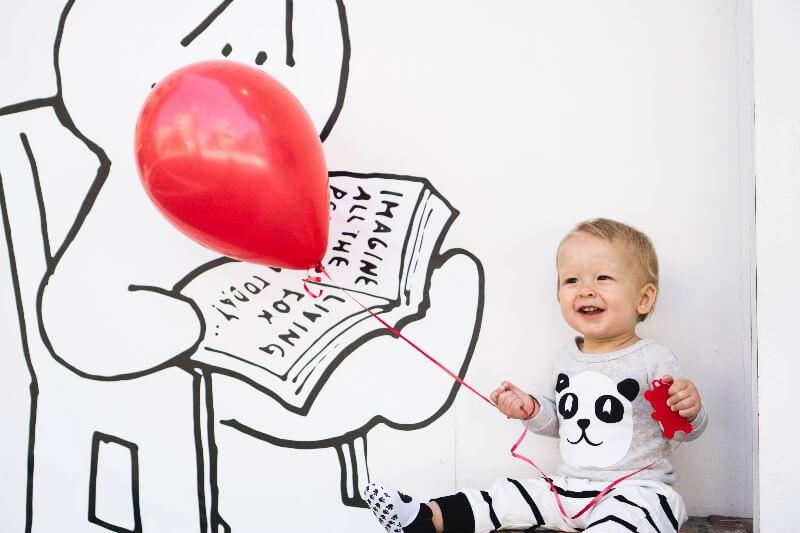 赤い風船を持った笑顔の赤ちゃん