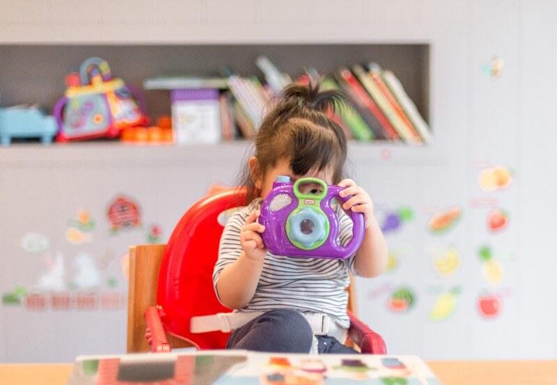 ポニーテールの子どもがおもちゃのカメラで遊んでいる