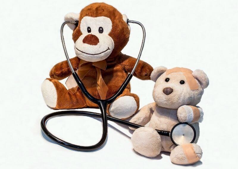 聴診器で診察しているサルと患者のくまのぬいぐるみ