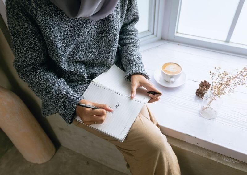 窓際でコーヒーを飲みながら女性ノートに文字を書く女性
