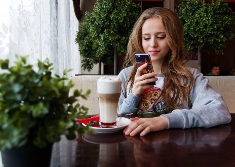 カフェラテを飲みながらスマホを触る女性